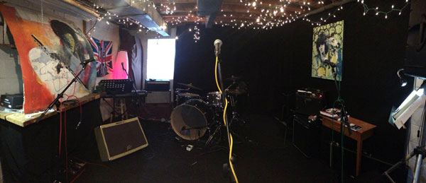 Microphone, drums, amplifiers and a stylized painting of Jimi Hendrix decorate the Jam Class rehearsal space